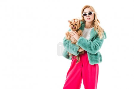 Attractive young woman dressed in fur coat holding cute Yorkie isolated on white