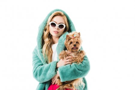 Blonde woman in fir coat hugging Yorkshire terrier isolated on white