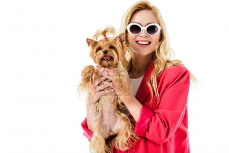 Blonde woman in pink clothes holding cute dog isolated on white