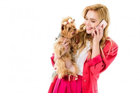 Blonde woman in pink clothes talking on phone and holding cute dog isolated on white