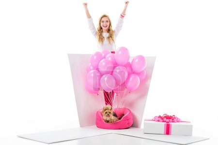 Happy young woman by gift box with yorkie dog and pink balloons isolated on white