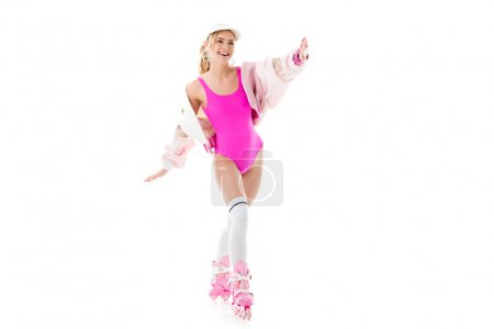 Blonde woman in pink swimsuit having fun on roller skates isolated on white