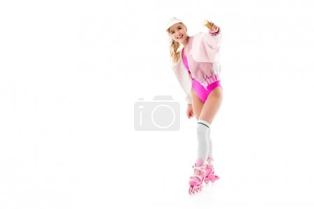 Attractive young woman in pink roller skates showing ice cream isolated on white