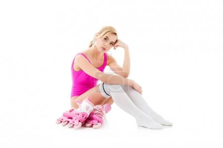 Young girl wearing pink swimsuit sitting by roller skates isolated on white