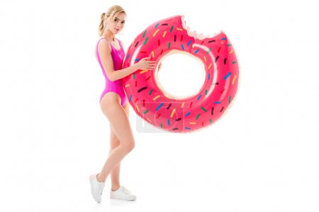 Young girl wearing pink swimsuit holding doughnut swim ring isolated on white