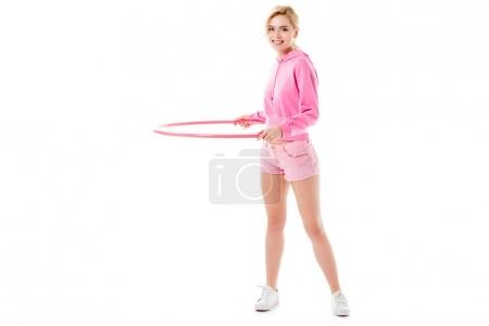 Young girl wearing pink exercising with hula hoop isolated on white