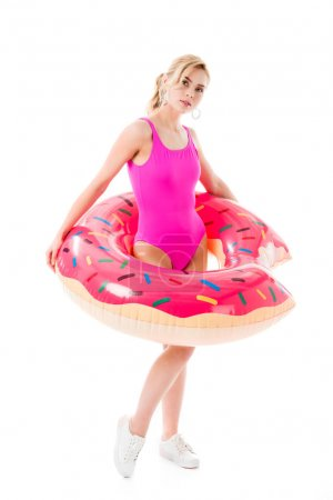 Attractive young woman dressed in pink swimsuit holding doughnut swim ring isolated on white