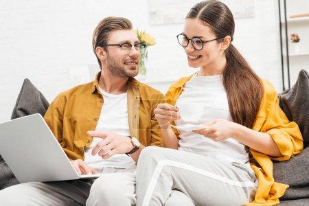 Photo pour Couple heureux avec café et ordinateur portable assis sur le canapé ensemble à la maison - image libre de droit