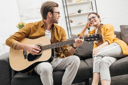 happy young man playing guitar for happy girlfriend