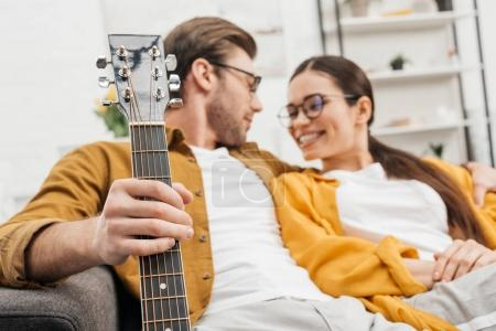smiling couple with guitar sitting on couch at home