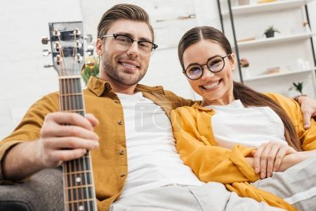 happy relaxed couple with guitar sitting on couch at home