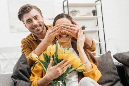 heureux homme jeune qui couvre les yeux de la petite amie et la présentation de son bouquet