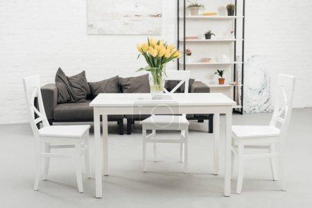Photo pour Intérieur du salon blanc avec des Tulipes jaunes dans un vase sur la table - image libre de droit