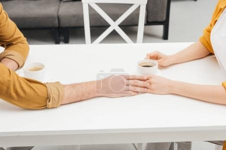 cropped shot of couple drinking coffee together and holding hands