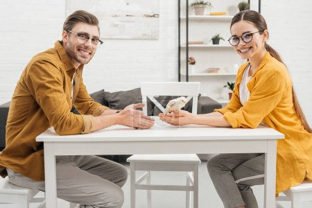 young happy couple sitting with little chick on table