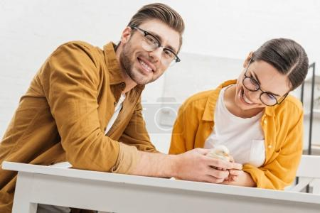 young happy couple with little chick on table at home