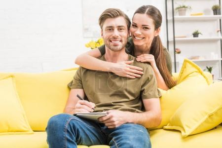 young man writing in notebook while his girlfriend embracing him from behind on couch at home