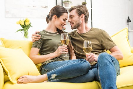 young passionate couple drinking wine together on couch at home