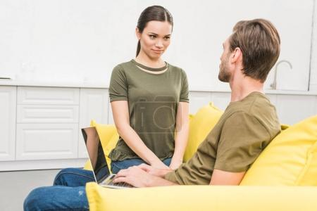 young woman sitting in front her boyfriend while he working at home with laptop