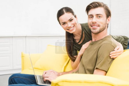 handsome young man working at home with laptop while his girlfriend embracing him from behind