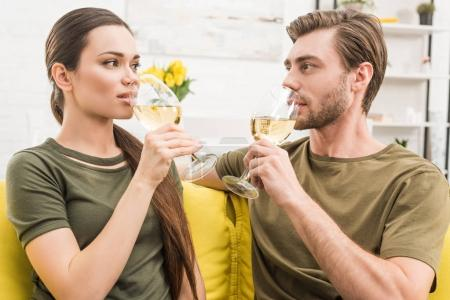 young couple drinking wine together on couch at home