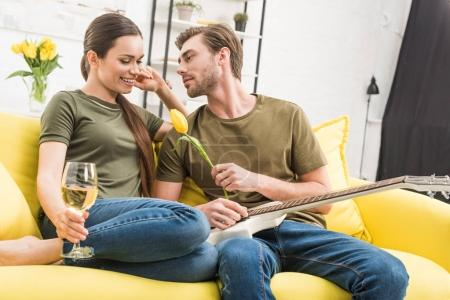 man with electric guitar presenting tulip flower to happy girlfriend while she holding glass of wine on couch at home