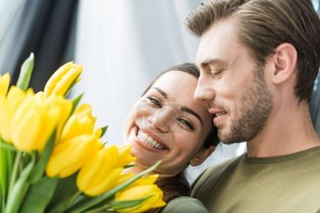 close-up shot of man presenting yellow tulips to happy girlfriend