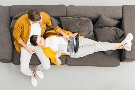 Foto de Vista superior de la mujer tendido en las rodillas del novio y trabajando con el portátil en acogedor sofá en casa - Imagen libre de derechos