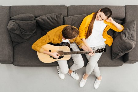 top view of man playing guitar to his girlfriend on couch at home