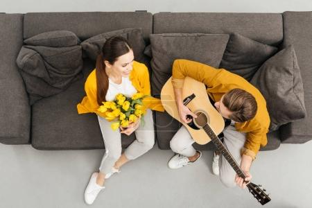 overhead view of man playing guitar to his girlfriend while she holding bouquet on couch at home