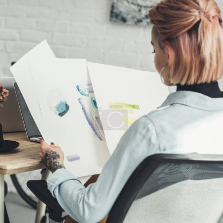 back view of tattooed designer looking at sketches at workplace in office