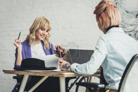 selective focus of young blogger and designer at workplace in office