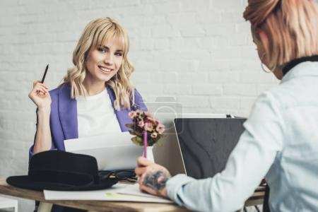 selective focus of smiling blogger and designer at workplace in office