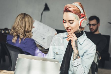 selective focus of tattooed businesswoman in headphones at workplace in office