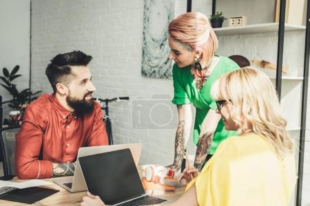 group of young creative workers discussing new project together in office