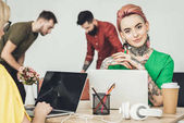 selective focus of young designer sitting at workplace with colleague while businessmen playing table football in office