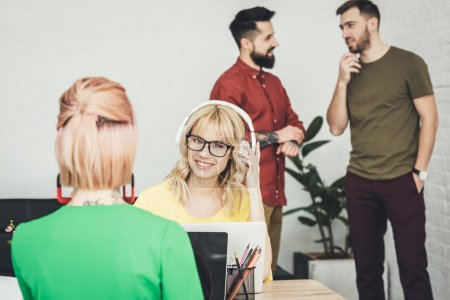 selective focus of young smiling blogger in headphones and colleagues talking behind in office