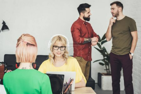 selective focus of young blogger in headphones and colleagues talking behind in office