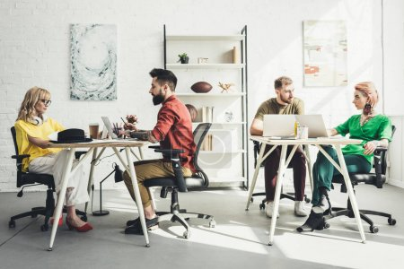 group of young creative workers working on project in office