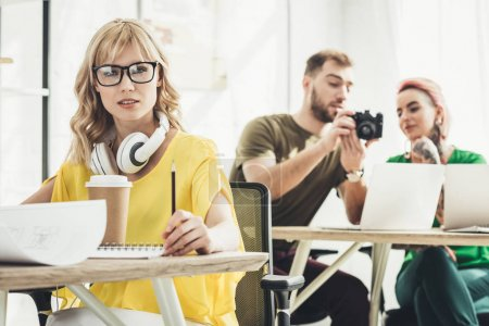 selective focus of young blogger with headphones looking at camera and colleagues working behind in office