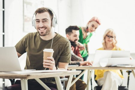 selective focus of smiling man in headphones with coffee to go and creative colleagues working behind in office
