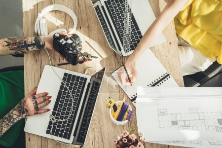 overhead view of blogger and photographer working at table together in office