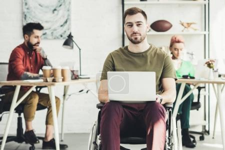 Photo for Selective focus of smiling disabled man with laptop and colleagues working behind in office - Royalty Free Image