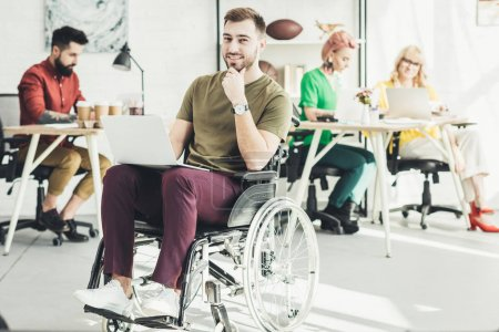 selective focus of smiling disabled businessman with laptop and colleagues working behind in office