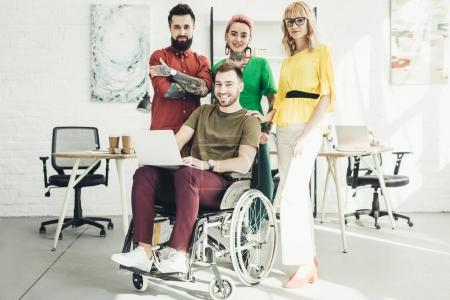 smiling disabled businessman with laptop and colleagues standing behind in office
