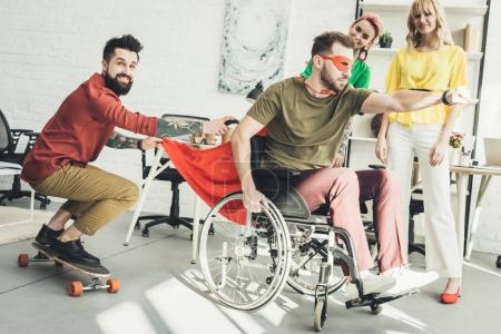 Photo for Disabled businessman in superhero costume with colleague on skateboard and businesswomen behind in office - Royalty Free Image