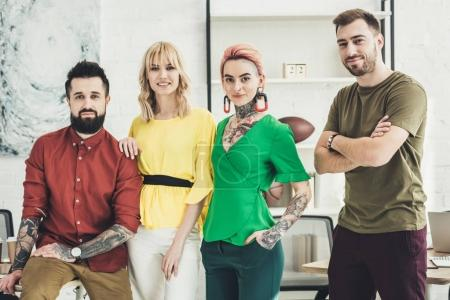 portrait of group of young stylish creative workers looking at camera in office