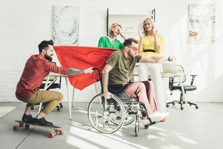 disabled businessman in superhero costume with colleague on skateboard and businesswomen behind in office