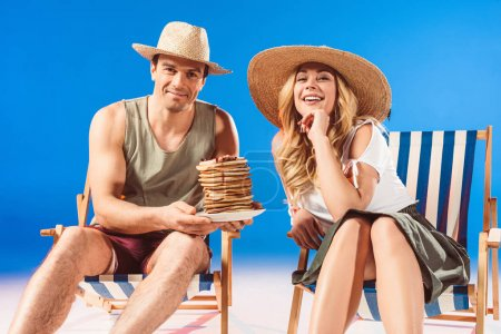 Man holding stack of pancakes and woman resting in deck chairs on blue background
