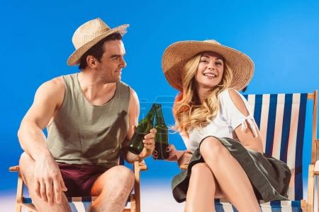 Man and woman toasting with beer bottles resting in deck chairs on blue background